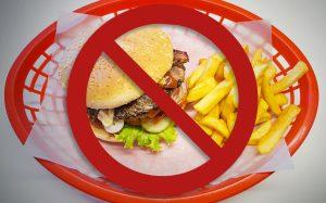 Teller mit Hamburger und Pommes mit Verbotsschild