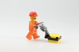 Lego Figur mit Kehrmaschine handgeführt