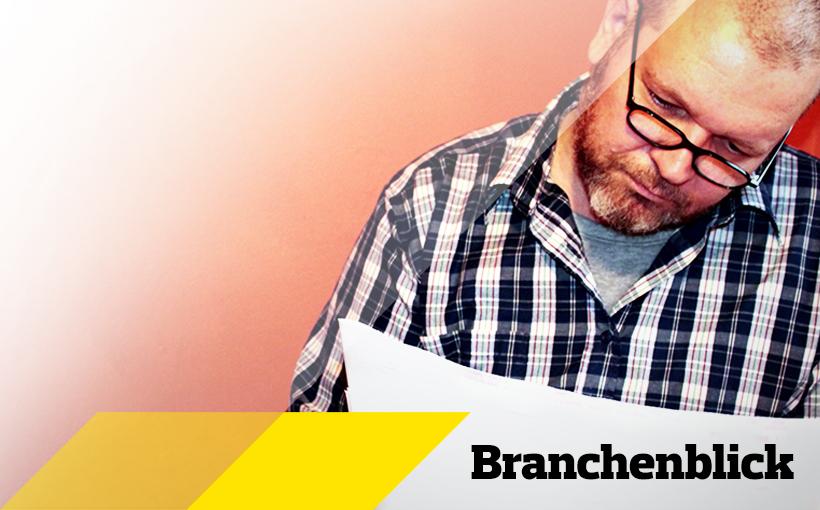 Handwerker mit Brille liest eine Zeitung